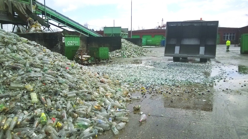 unikátní příležitost vidět ničení zabaveného alkoholu: na lopatu bagru jsou vyskládány lahve z palety, které jsou pak z výšky vysypány na zem